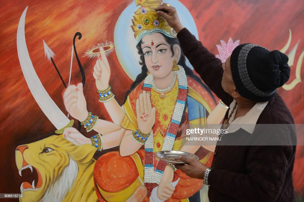 Indian artist Mohan Mehra paints the goddess Maa Durga at a temple in Amritsar on January 18 2018 Mehra offers his services free of cost to decorate..
