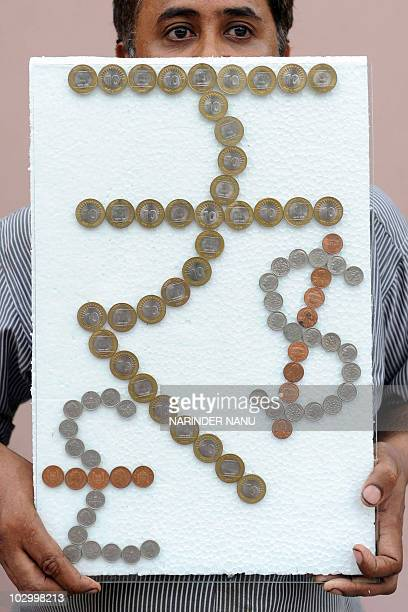 Indian artist Shanti Savroop his depiction of the new Indian rupee currency symbol made of Indian rupee coins beside the US dollar and British pound...