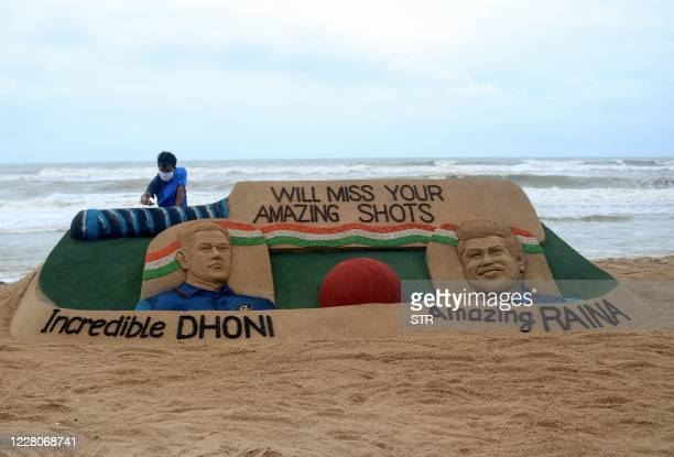 Indian artist Sudarsan Pattnaik gives the final touches to his sand sculpture depicting Indian cricket superstar M.S. Dhoni and fellow World Cup...