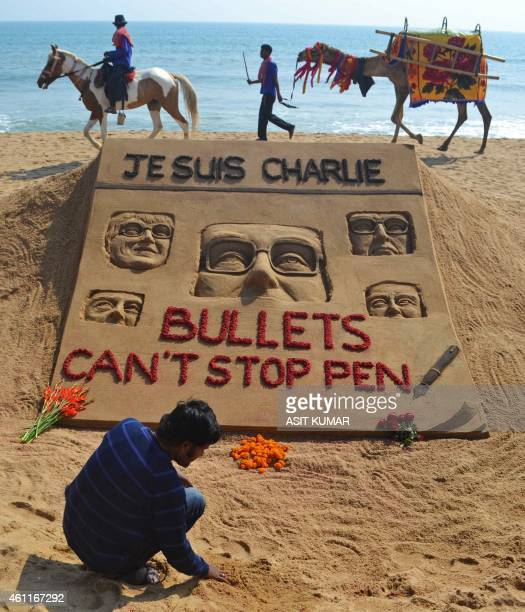 Indian artist Sudarsan Pattnaik is pictured with his sand sculpture in tribute of those who lost their lives in the January 7 attack by gunmen on...