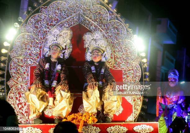 Indian artists dressed as Hindu God Rama and his brother Lakshman sit on a tableau during a religious procession known as 'Karan Ghoda' during a...
