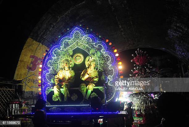 Indian artists dressed as Hindu God Rama and his brother Lakshman sit on a tableau as they pass through a street during a religious procession known...