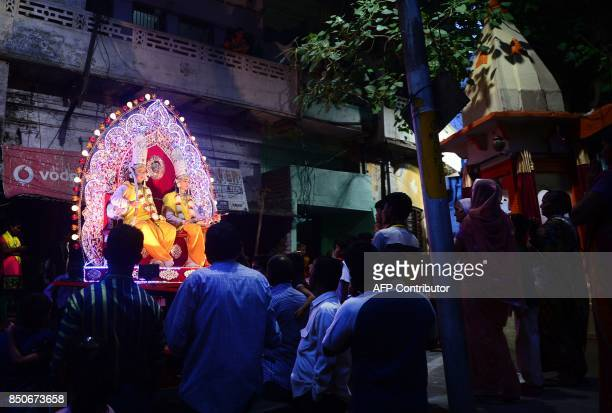 Indian artists dressed as Hindu god Rama and his companion Laxman sit in a tableau passing through a narrow street during a Dussehra festival...
