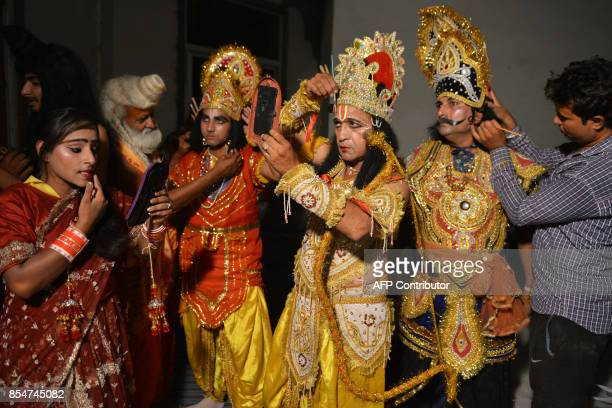 Indian artists dressed as Hindu Lord Rama Sita Laxman and Ravan put on their makeup before performing the 'Ramleela' the story of Lord Rama ahead of...