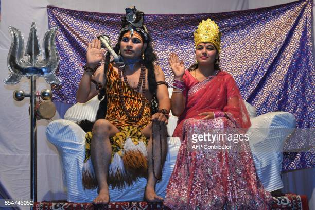 Indian artists dressed as Hindu Lord Shiva and Parvati perform during the 'Ramleela' the story of Lord Rama ahead of the Hindu festival of Dussehra...