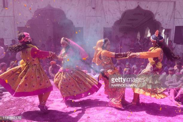 Indian artists dressed as Lord Krishna and Radha perform traditional folk dance during Holi festival celebrations at a temple in Amritsar on March 21...