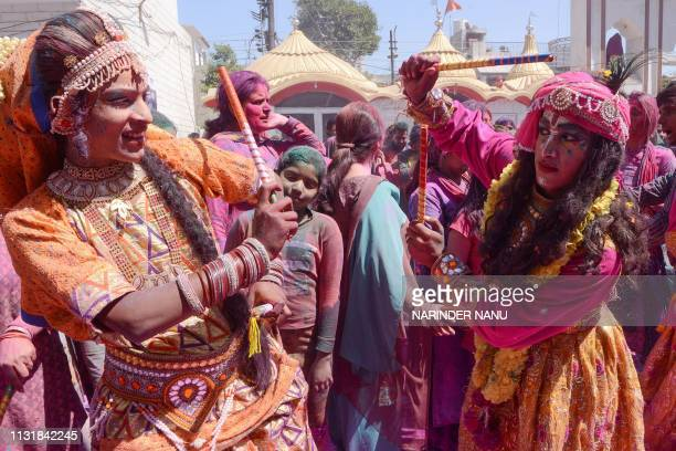 Indian artists dressed as Lord Krishna and Radha perform traditional folk dance Dandiya Raas during Holi festival celebrations at a temple in...