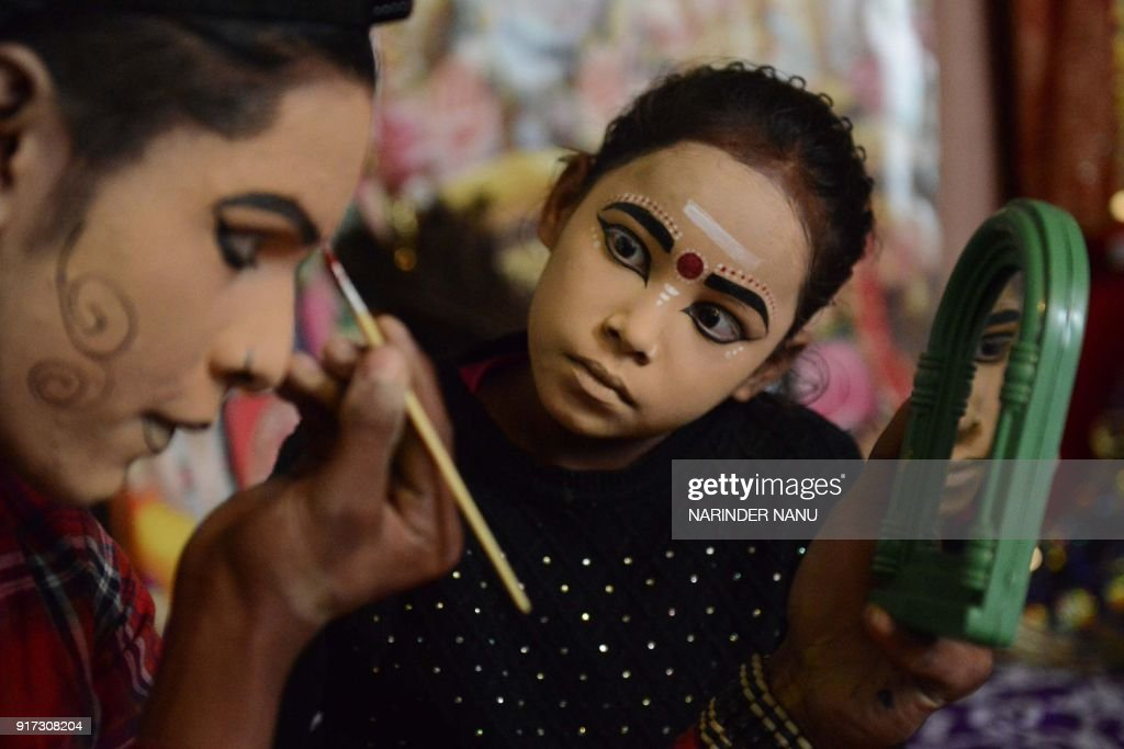 Indian artists dressed as Lord Shiva and goddess Durga apply makeup before performing a religious function on the eve of the Maha Shivratri festival..