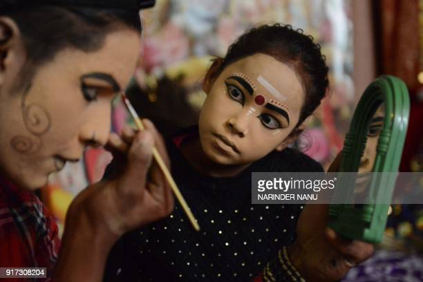 Indian artists dressed as Lord Shiva and goddess Durga apply makeup before performing a religious function on the eve of the Maha Shivratri festival...