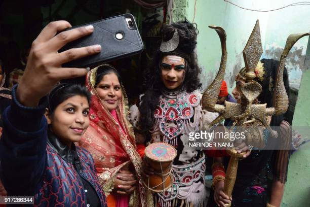 Indian artists dressed as Lord Shiva takes selfie pictures during a religious function on the eve of the Maha Shivratri festival at a temple in...