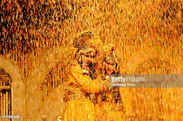 Indian artists dressed up as Hindu Lord Krishna and his consort Radha are showered with flower petals during Holi celebrations at Shri Chaitanya Prem...