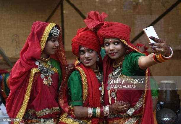 TOPSHOT Indian artists from central India of Madhya Pradesh take selfie before performing in a cultural event organised by Indira Gandhi National...