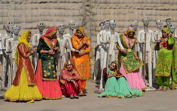 Indian artists wait for the arrival of Indian Prime Minister Narendra Modi and French President Francois Hollande at the Rock Garden in Chandigarh on.