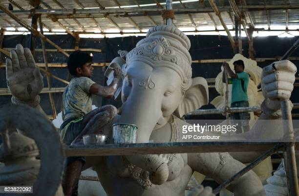 Indian artists work on idols of the elephantheaded Hindu god Lord Ganesha at a workshop ahead of the Ganesh Chaturthi festival in Mumbai on July 28...