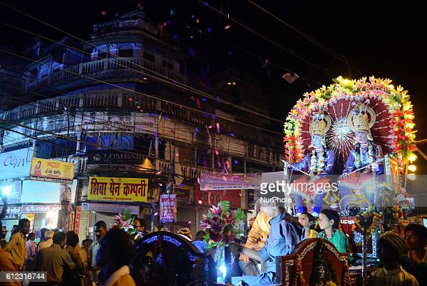 Indian artists,dressed as Hindu God Ram and brother Laxman, sit on a chariot as they take part in a religious procession 'Ram Barat' ,ahead of...