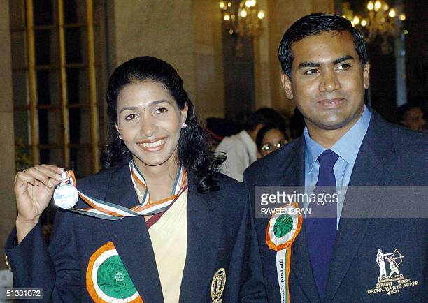 Indian athlete Anju Bobby George show her Rajiv Gandhi Khel Ratna Sports award India's highest award for sports as she stands with her husband...
