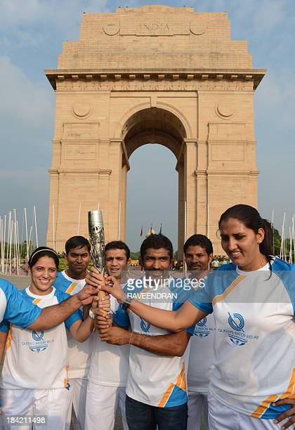 Indian athletes Krishna Poonia and Yogeshwar Dutt hold the Commonwealth Games Queens Baton in front of the India Gate monument in New Delhi on...