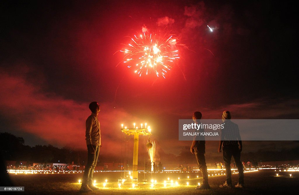 Indian athletes watch fireworks at the Madan Mohan Malviya stadium on the eve of the Hindu festival of Diwali in Allahabad on October 29, 2016. Diwali, the Festival of Lights, marks victory over evil and commemorates the time when Hindu god Lord Rama achieved victory over Ravana and returned to his kingdom Ayodhya. / AFP / SANJAY