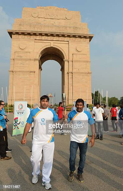 Indian athletes Yogeshwar Dutt holds the Commonwealth Games Queens Baton in front of the India Gate monument in New Delhi on October 12 2013 The...