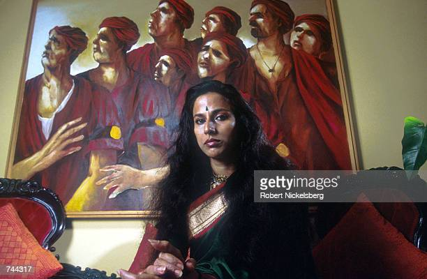 Indian author Shobha De nicknamed the Jackie Collins of Bombay for her spicy hot writing on sex poses at home near a painting by Indian artist Subash...
