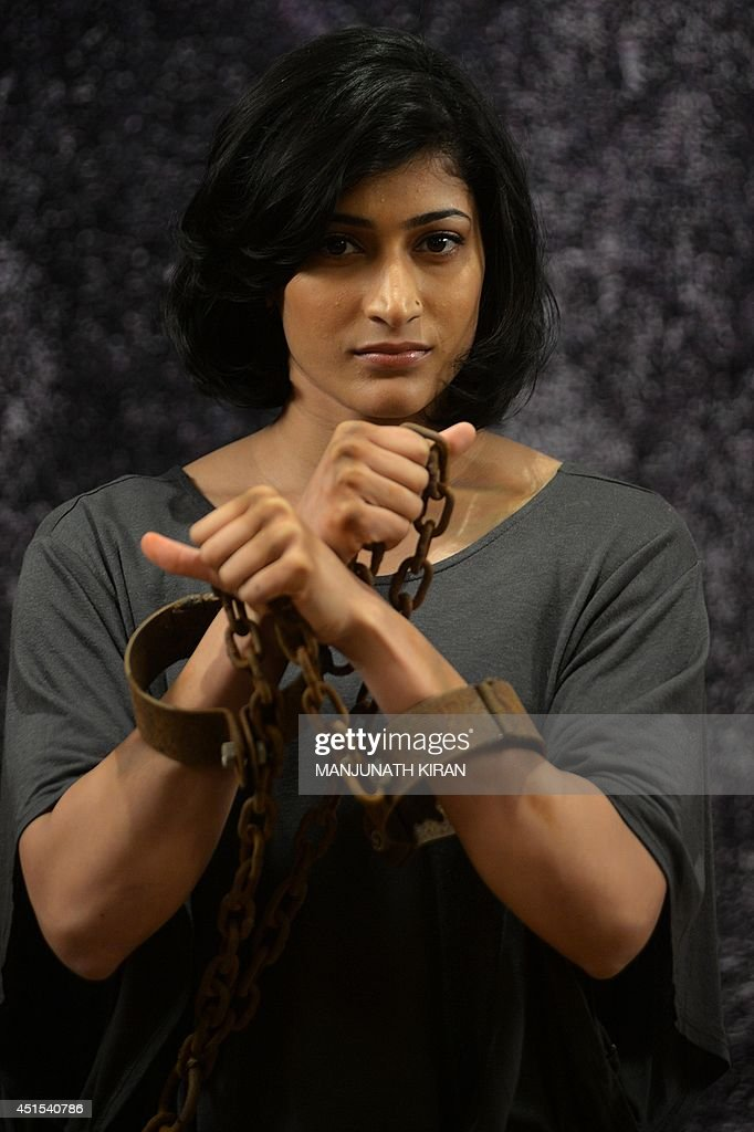 Indian badminton women's doubles champion, Ashwini Ponnappa stands confined in chains and shackles as she poses for a photograph during a PETA campaign against the use of animals in circuses, in Bangalore on July 1, 2014. The People for Ethical Treatment of Animals (PETA) allege that animals in circuses are subjected to chronic confinment, physical abuse and psychological torment by handlers. AFP PHOTO/Manjunath KIRAN