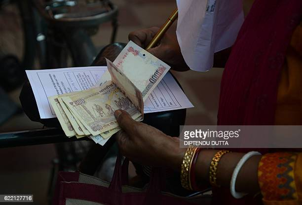 Indian banking customer Sreya Paul fills a form for currency exchange outside a State Bank of India branch where others gathered to deposit and...