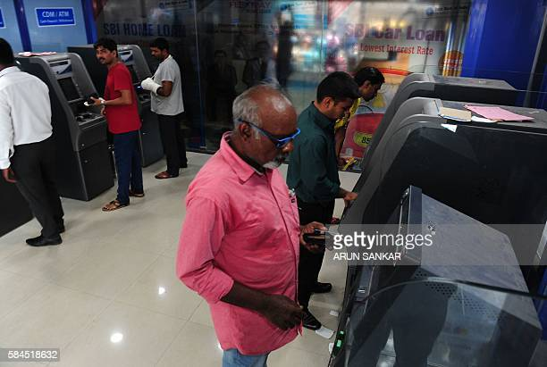 Indian banking customers withdraw cash from ATMs in Chennai on July 29 2016 Banking operations across the country were affected as employees in 40...