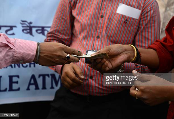 Indian banking staff of the State Bank of India assist customers to withdraw money with the use of a mobile banking machine at Siliguri District...