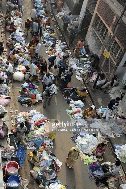 Indian bargain hunters browse through clothing at a second hand clothing market in Kolkata on February 11 2009 The used clothing market held daily on...