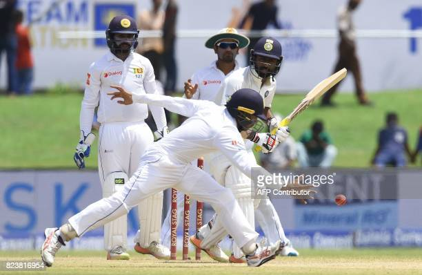 Indian batsman Abhinav Mukund plays a shot as Sri Lankan cricketer Kusal Mendis attempts to stop the ball during the third day of the first Test...