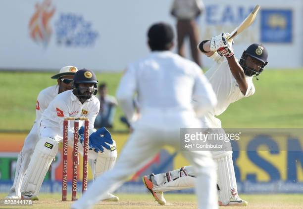 Indian batsman Abhinav Mukund plays a shot as Sri Lankan wicketkeeper Niroshan Dickwella looks on during the third day of the first Test match...