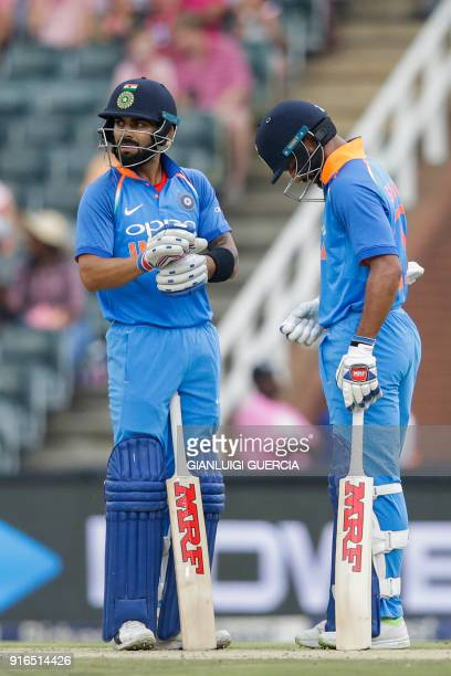 Indian batsman and Captain Virat Kohli chats with Indian batsman Shikhar Dhawan after scoring a four during the fourth One Day International cricket...