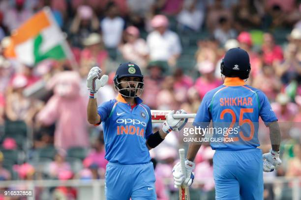 Indian batsman and Captain Virat Kohli congratulates Indian Batsman Shikhar Dhawan after scoring half century during the fourth One Day International...