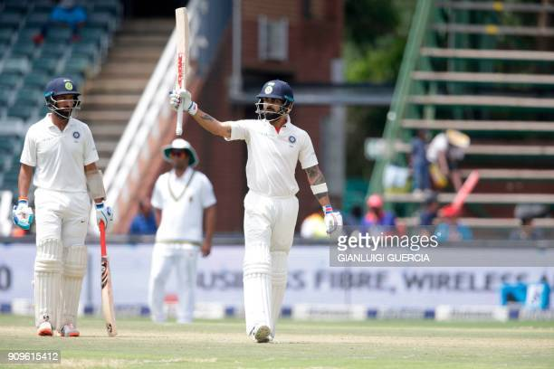 Indian batsman and Captain Virat Kohli raises his bat as he celebrates scoring a half century during the first day of the third cricket Test match...