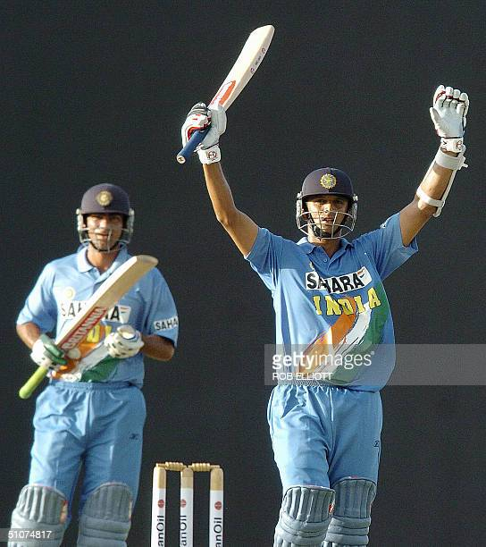 Indian batsman and vice-captain Rahul Dravid holds his bat high as he acknowledges the crowd's applause after his century as team mate Mohammed Kaif...