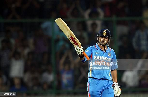 Indian batsman Gautam Gambhir raises his bat after completing his halfcentury during the 2nd One Day International cricket match between India and...