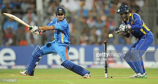 Indian batsman Gautum Gambhir cuts a ball away as Sri Lankan wicketkeeper Kumar Sangakkara looks on during the ICC Cricket World Cup 2011 between...