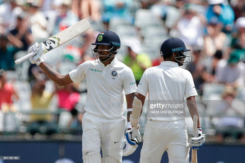 Indian batsman Hardik Pandya (L) raises his bat as he celebrates scoring half century (50 runs) during the second day of the first Test cricket match between South Africa and India at Newlands cricket ground on January 6, 2018 in Cape Town, South Africa. /