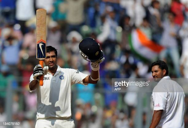 Indian batsman Ravichandran Ashwin is watched by West Indies bowler Ravi Rampaul as he celebrates after scoring a century during the fourth day's...