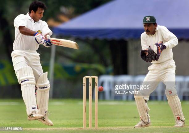 Indian batsman Robin Singh chops down on a ball as Canada's wicketkeeper Ramnarais Karamchandra looks on in their group match at the XVI Commonwealth...