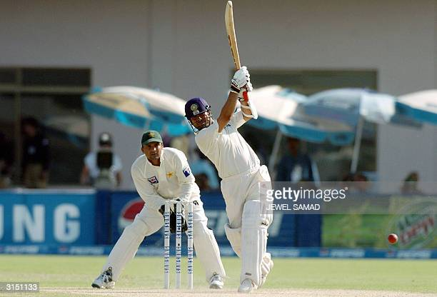 Indian batsman Sachin Tendulkar hits a boundary off Pakistani spin bowler Saqlain Mushtaq as wicketkeeper Moin Khan looks on during the second day of...