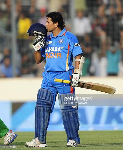 Indian batsman Sachin Tendulkar kisses his helmet after scoring his hundred century during the one day international Asia Cup cricket match between...
