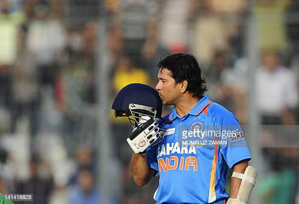 Indian batsman Sachin Tendulkar kisses his helmet after scoring his hundred century as he is watched by Bangladeshi cricketer Shakib Al Hasan during...