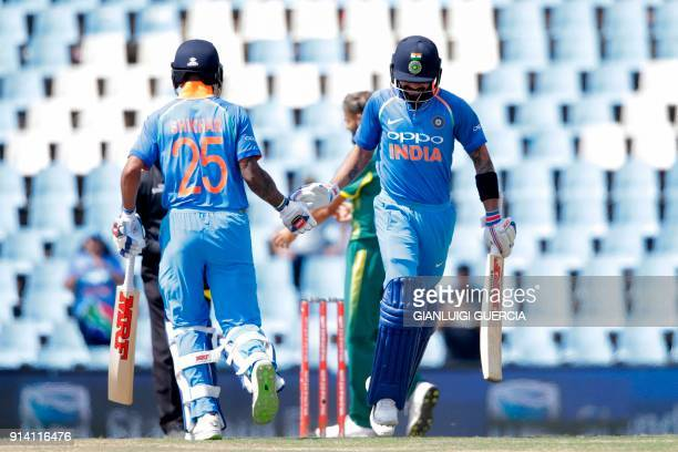 Indian batsman Shikhar Dhawan and Captain Virat Kohli tape in each others hands as they take the last two run to win the match during the second day...