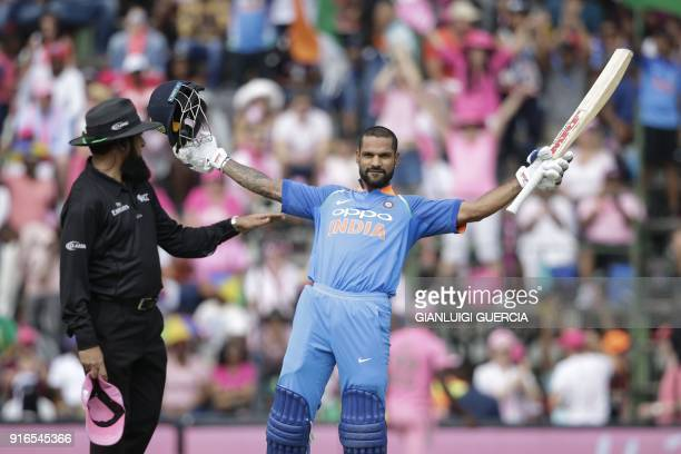 Indian batsman Shikhar Dhawan raises his bat and helmet as he celebrates scoring a century during the fourth One Day International cricket match...