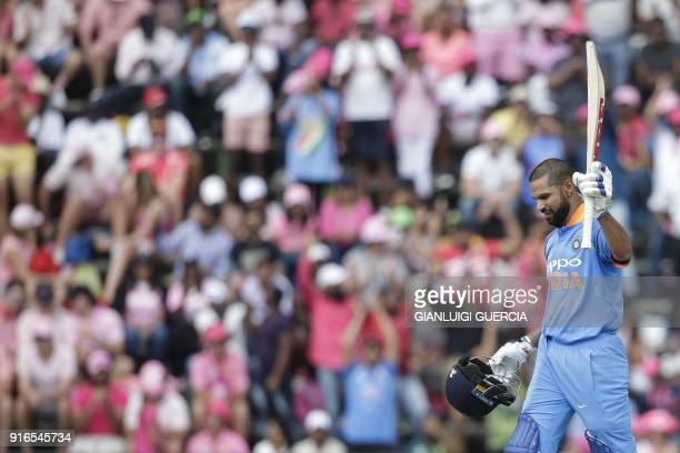 Indian batsman Shikhar Dhawan raises his bat and helmet as he celebrates scoring a century during the fourth One Day International cricket match...