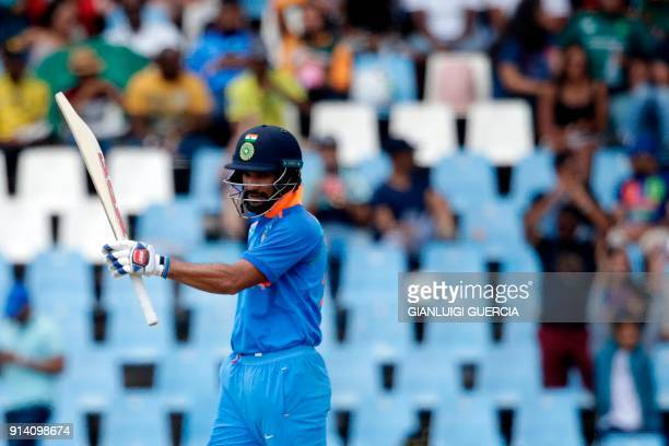 Indian batsman Shikhar Dhawan raises his bat as he celebrates scoring a half century during the second day of the One Day International cricket match...