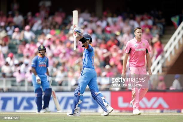 Indian batsman Shikhar Dhawan raises his bat as he celebrates scoring half century during the fourth One Day International cricket match between...