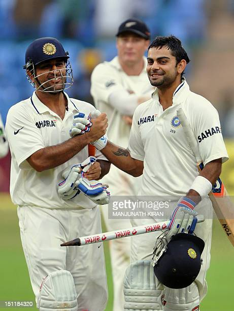 Indian batsman Virat Kohli and captain Mahendra Singh Dhoni celebrate after India won the second Test match against New Zealand at the M Chinnaswamy...