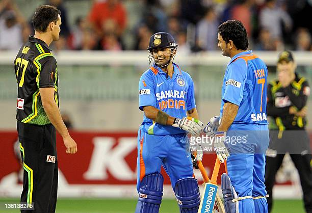 Indian batsmen MS Dhoni and Gautam Gambhir congratulate each other as Australian bowler Clint McKay looks on after India defeated Australia in the...